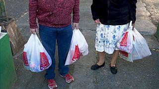 Dos mexicanos cargan bolsas de plástico tras salir de la compra