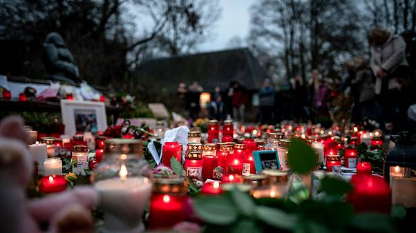 Flowers and candles left at a makeshift memorial site in front of the burned-out monkey house at Krefeld Zoo