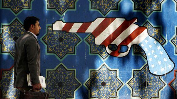 An Iranian man walks pass an anti-U.S. graffiti painted on the wall of the former U.S. Embassy in Tehran