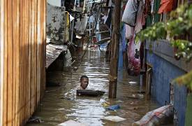 A man swims in flood water in a low-income neighborhood in Jakarta, Indonesia. 2 January 2020. Severe flooding in the capital as residents celebrated the new year has killed s