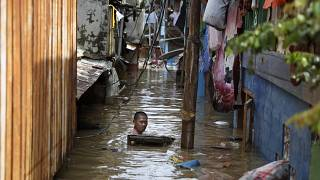 A man swims in flood water in a low-income neighborhood in Jakarta, Indonesia. 2 January 2020.
