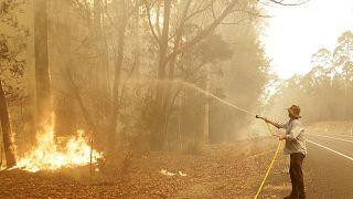 رجل يستخدم خرطوم مياه لمحاربة حريق بالقرب من مورويا في أستراليا، 4 يناير 2020