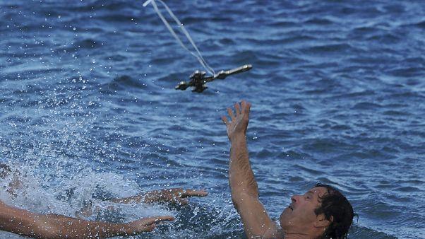 سباح يحاول خطف صليب رماه كاهن أرثودكسي في الماء يوم الاحتفال بعيد الظهور في جزيرة قبرص.