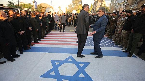 Iraqi paramilitaries walk on pictures Trump and Netanyahu