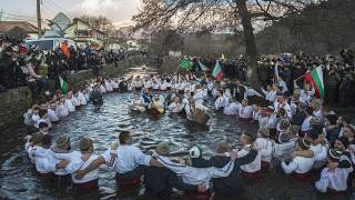 Bulgarians sing, play bagpipes and chaindance in the icy waters during Epiphany ritualin