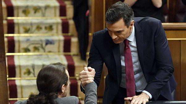 Le socialiste Pedro Sanchez, après son investiture, serrant la main de Pablo Iglesias, le chef de file de Podemos, le 7 janvier 2020 à la Chambre des députés à Madrid.