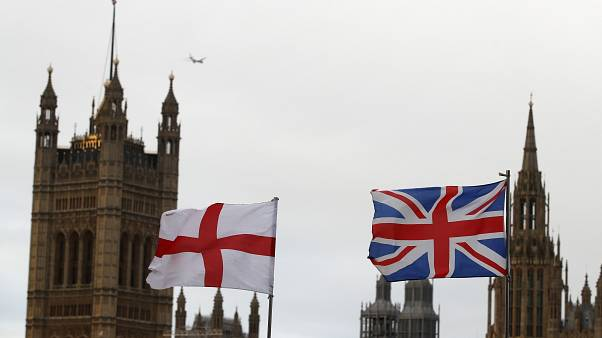 A British and an English flag wave in front of Houses of Parliament in London, Saturday, Dec. 14, 2019.