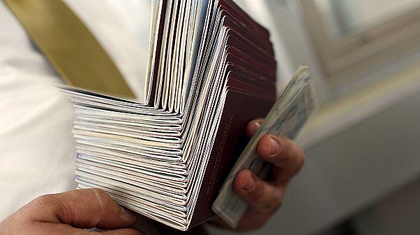 شخص يمسك بعدد من جوازات السفر