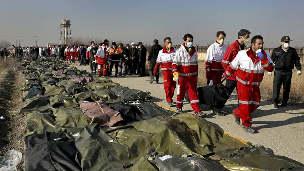 Rescue workers carry the body of a victim of an Ukrainian plane crash in Shahedshahr, southwest of the capital Tehran, Iran, Wednesday, Jan. 8, 2020.
