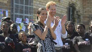 Britain's Prince Harry and Meghan, Duchess of Sussex greet youths on a visit to the Nyanga Methodist Church in Cape Town, South Africa on September 23, 2019.