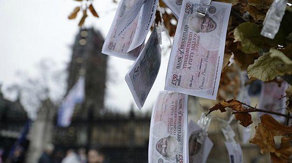 """أوراق نقدية مزيفة قيمتها 350 جنيه استرليني، عليها وجه رئيس الحكومة البريطانية بوريس جونسون، وهي تتدلى من """"شجرة المال السحرية"""" التي وضعها المتظاهرون المناهضون لـ""""بريكست"""""""