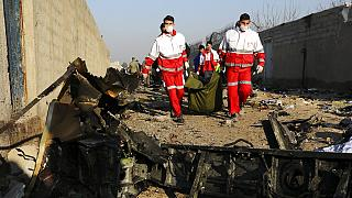 Rescue workers carry the body of a victim of an Ukrainian plane crash in Iran