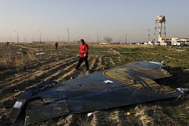 A rescue worker searches the scene where the Ukrainian plane crashed near the capital Tehran, Iran.