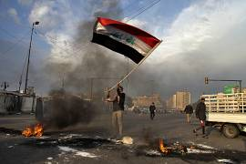 A protester waves the national flag while demonstrators set fire to close streets near Tahrir Square during a demonstration against the Iranian missile strike in Baghdad, Iraq