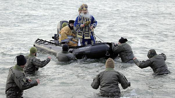 Military divers walk to a boat carrying Orthodox archbishop Teodosie during an Epiphany religious service in Constanta, Romania. 6 January, 2020.