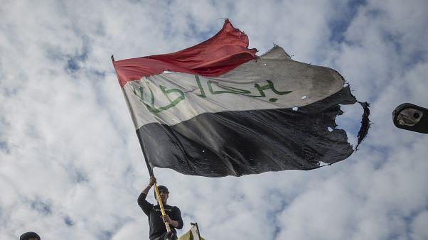 عراقي يحمل العلم الوطني خلال مظاهرة بساحة التحرير في بغداد