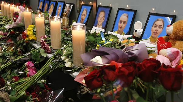 Tributes are placed in front of portraits of the flight crew members of the downed Ukrainian plane, in Borispil international airport, near Kyiv, Jan. 11, 2020.