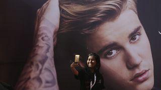 إحدى معجبات المغني الكندي جاستن بيبر تأخذ صورة سيلفي أمام صورته قبل حفل موسيقي له في مومباي، مايو 2017.