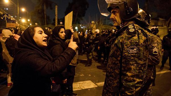 An Iranian woman at a vigil for victims of the Ukraine plane disaster talks to policeman at Amri Kabir University, Tehran