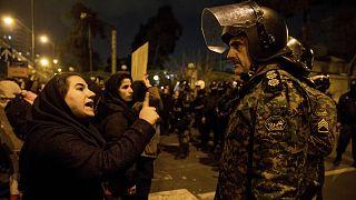 متظاهرة إيرانية تتحدث لأحد أفراد الأمن