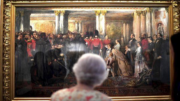 Queen Elizabeth II looks at a painting of Queen Victoria