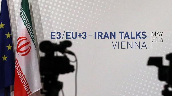 Cameras stand in front of flags from the EU and Iran and poster of the Iran talks