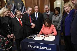 House Speaker Nancy Pelosi of Calif., signs the resolution to transmit the two articles of impeachment against President Donald Trump to the Senate for trial on Capitol Hill.