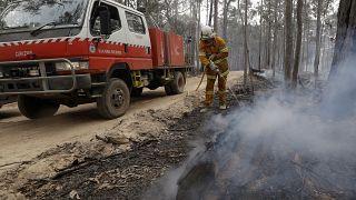A firefighter patrols a controlled fireat a wildfire near Bodalla, Australia