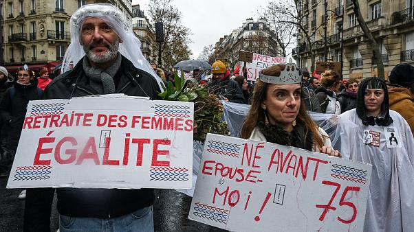 """Protesters walk with placards reading """"Equality for women's pension"""" (L) and """"Born before 1975: mary me"""" during a demonstration on December 12, 2019"""