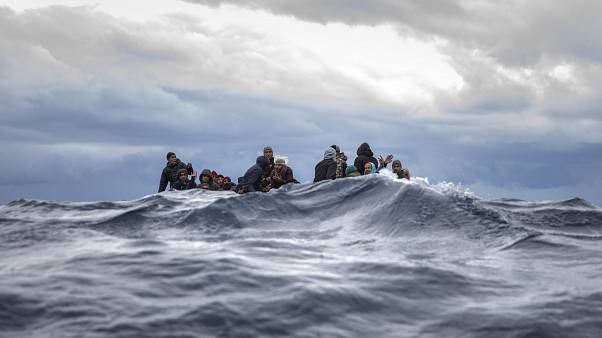 Men from Morocco and Bangladesh on an overcrowded wooden boat off the Libyan coast