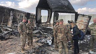 جنود أمريكيون يقفون على آثار قصف صاروخي إيراني على قاعدة عين الأسد الأمريكية في العراق
