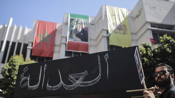 """يحمل المتظاهرون تابوتا رمزيا مكتوبا عليه """"العدالة""""، خلال مسيرة تندد بالأحكام الشديدة ضد نشطاء الحراك، في الدار البيضاء، المغرب، الأحد 8 يوليو تموز 2018"""