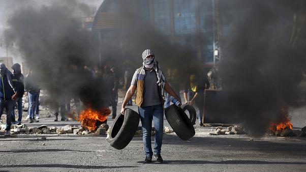 متظاهر فلسطيني يحمل إطارات خلال مظاهرات في رام الله