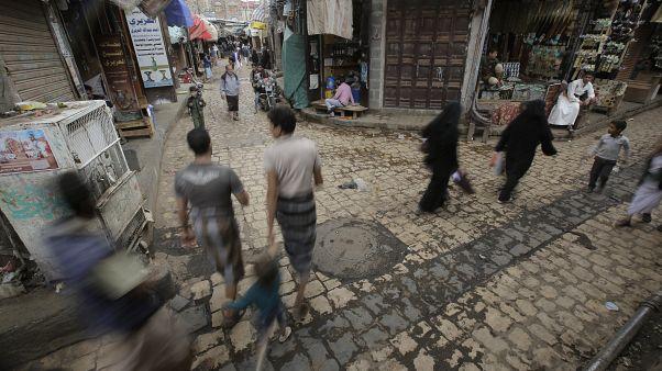 يمنيون يمشون أمام البائعين في أسواق صنعاء القديمة، 28 سبتمبر 2019
