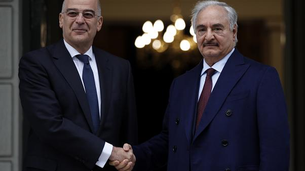 Libyan Gen. Khalifa Hafter, right, and Greek Foreign Minister Nikos Dendias shake hands before their meeting in Athens, Friday, Jan. 17, 2020