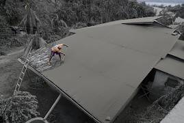 A resident clears volcanic ash from his roof in Laurel, Batangas province, the southern Philippines on Tuesday, 14 January 2020