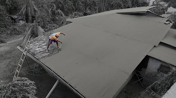 A resident clears volcanic ash from his roof in Laurel, Batangas province, the southern Philippines on Tuesday, 14 January, 2020