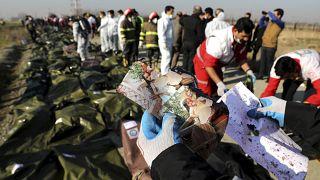 أحد عمال الإنقاذ يحمل صورا وجدت في موقع تحطم الطائرة الأوكرانية في طهران - إيران