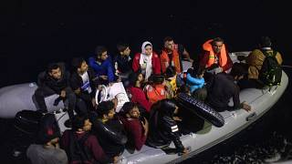 Refugees and migrants on a plastic boat approach a Greek Coast Guard ship in September 2019