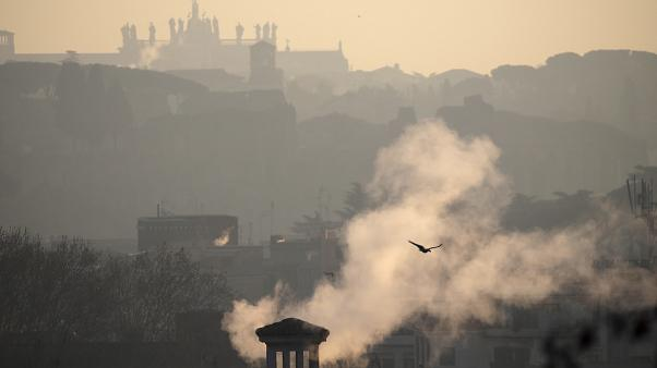 Smoke billows from chimneys of residential buildings in Rome, Friday, Jan. 17, 2020.