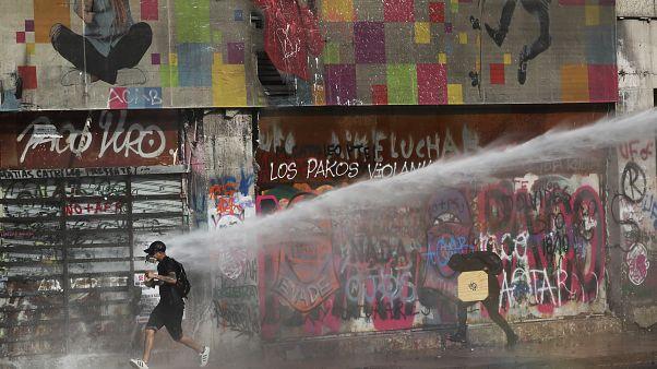 Un manifestant tente d'échapper à un jet de canon à eau, Santiago, Chili, le 17 janvier 2020