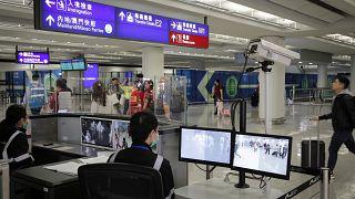 مسؤول مراقبة الصحة يقوم باستخدام الماسح الضوئي لدرجة الحرارة للمسافرين في مطار هونغ كونغ
