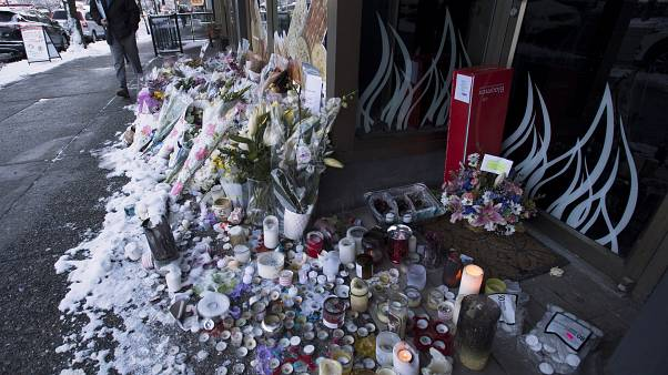 Snow-covered flowers and candles are seen outside of the family bakery of Ayeshe Pourghadheri and her daughter Fatemah Pasavand in North Vancouver, B.C.