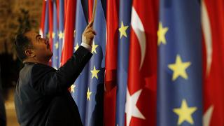 An official adjusts Turkey's and European flags prior to a meeting between EU and Turkey