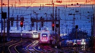 Two train approach the main train station after the sun set in Frankfurt, Germany, Friday, Jan. 17, 2020. (AP Photo/Michael Probst)
