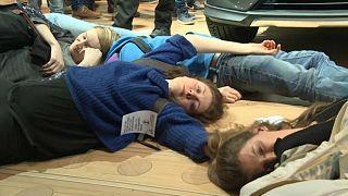 ناشطون يفترشون الأرض في معرض بروكسل للسيارات تعبيراً عن رفضهم لهذه الصناعة التي تشكّل خطراً على البيئة