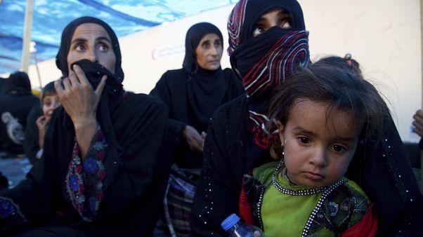 صورة للمشردين من النساء والأطفال يجلسون على الأرض عند نقطة تجميع غرب الموصل