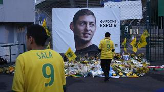 "Nantes team supporters in front of a poster of Emiliano Sala that says ""Let's keep hope"""
