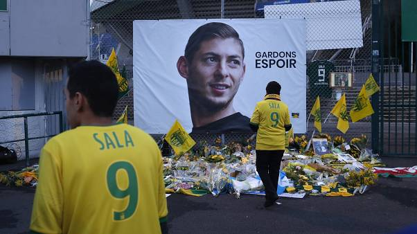 """Nantes team supporters in front of a poster of Emiliano Sala that says """"Let's keep hope"""""""