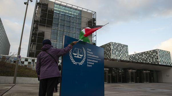 سيدة تحمل علم فلسطين أمام مبنى المحكمة الجنائية الدولية